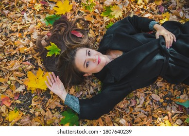 woman laying on the ground in autumn yellow leaves