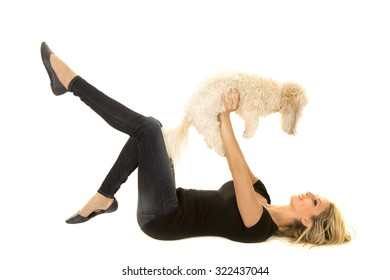 a woman laying on her back holding up her puppy.