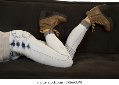 A woman laying on her couch with her jeans on and her feet kicked up.