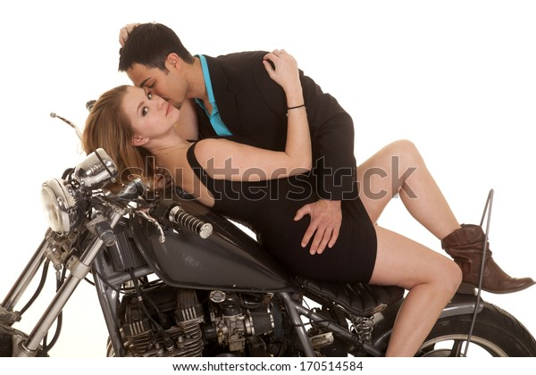 A woman  laying on her a motorcycle and her man is going in for a kiss on her cheek.