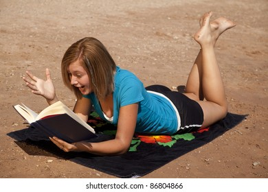 A woman laying on her towel reading a book with a shocked expression on her face.