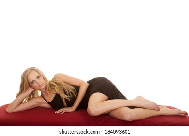 a woman laying on a red sheet in her black dress.