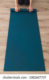 Woman laying out yoga mat in a studio