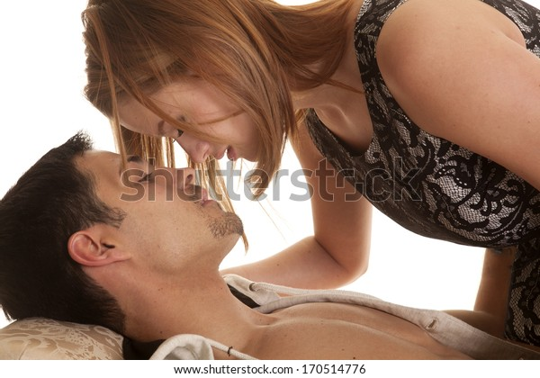 A woman is laying over a man about to kiss.