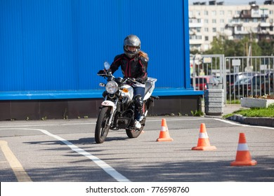 Woman L-driver driving slalom through the cones on training ground on small motorcycle