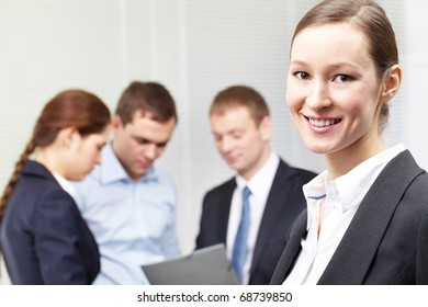 A woman leader standing against her colleagues