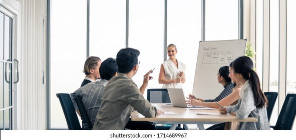 Woman leader working brainstorm to solve problem with team, presentation new idea. People discuss and smile on new challenge topic in meeting room. Business finance and communication planning concept.