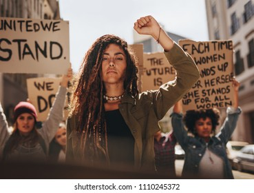 Woman leading a group of demonstrators on road. Group of female protesting for equality and women empowerment.