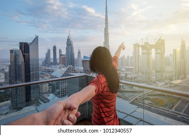 Woman is leading her partner and is pointing with her finger to the skyline of Dubai Downtown