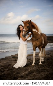 Woman leading horse by its reins. Horse riding on the beach. Love to animals. Asian woman wearing long white dress. Travel concept. Copy space. Bali, Indonesia