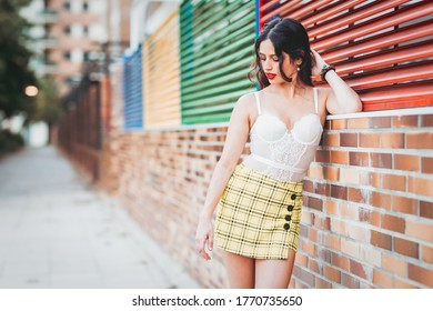 woman lean against a wall in a skort and bodysuite