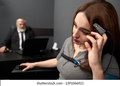 Woman leaning head on hand with finger sensor, looking away. Young woman examination with polygraph in grey room. Elderly man at black table with computer polygraph on background.