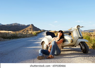 Woman leaning on motorbike and sidecar