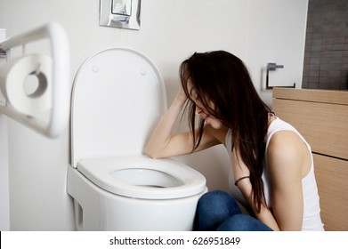 Woman leaning on open toilet seat at indoor bathroom
