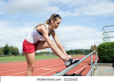 Woman leaning on a rail by the bleachers tying her shoe at a track. Vertically framed photo.