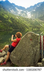 A woman leaning on a stone holds a phone in her hand and takes pictures of the 'Sea Eye' in Poland. 28/05/2018 - Morskie Oko, Poland.