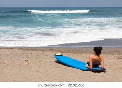 Woman leaning on surfboard watching surfers at Canggu (Batu Bolong) Beach, Bali, Indonesia