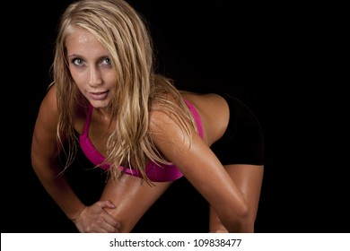 A woman leaning over with an intense expression on her face with sweat dripping off of her body.