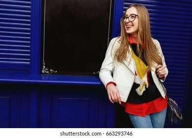 Woman leans to a blue door standing on the street