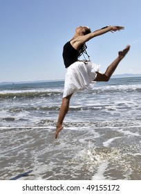 woman leaping in waves at beach