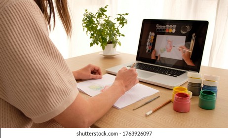 Woman learning to draw on an online course online sitting at home looking over her shoulder. Drawing lesson online on a laptop works on a computer