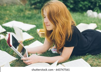 Woman learning with ebook reader and book. Choice between modern educational technology and traditional way method. Girl holding digital tablet. Contemporary education. Girl in the summer garden