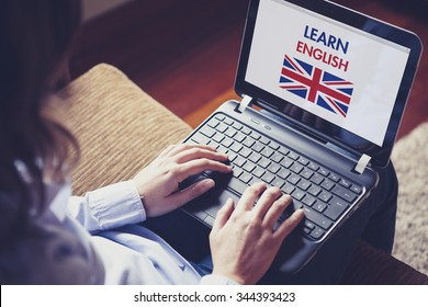 Woman learning english through internet with a laptop at home