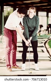 Woman learning to play golf with a golf trainer