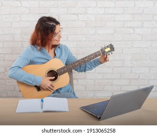 A woman is learning to play the guitar online. Remote music lesson