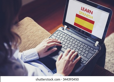 Woman learning Spanish language through internet with a laptop at home