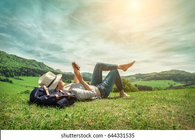 Woman leasure around the mountains with her phone and shootinh beautiful green fields view under sunlight on summer day.