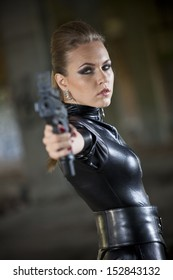 woman in leather catsuit aiming with a gun in the camera