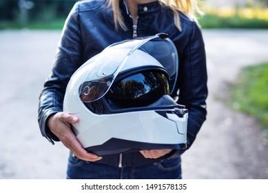 Woman in leather jacket holds motorcycle helmet