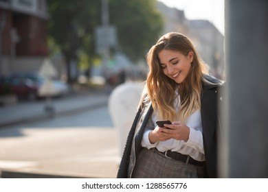 Woman with leather jacket using phone at urban street