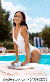 Woman leaving pool. Beautiful young slim woman leaving pool after nice swimming time