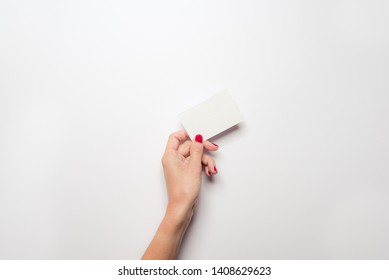 Woman left hand holding a blank business card.