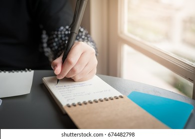 Woman left hand holding pen while writing on small notebook beside window. Freelance journalist working at home concept.