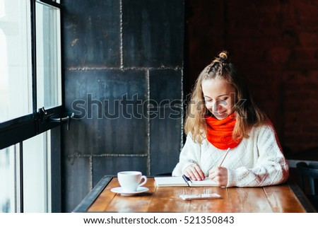 Woman left  hand writing journal on small notebook  in cafe with big window.