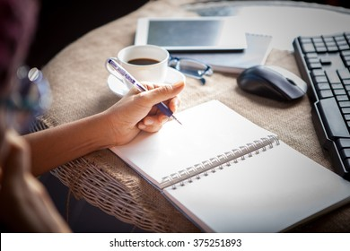 woman left hand writing on paper book ,on table shot