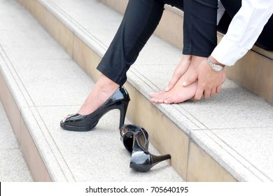 Woman with leg cramps and ankles from high heels. She sat on the stairs holding her leg.