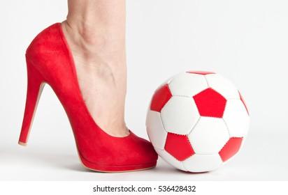 Woman leg in high heel shoe punch a soccer ball