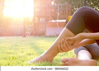 Woman leg pain, leg pain Sitting up on the grass in the playground. The morning sun light, healthy concept.