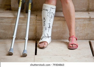 A Woman with leg in plaster and crutches