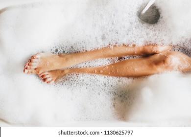 Weibliche Beine in Badeschaum. Draufsicht. Genießen und entspannen im Wellnesshotel