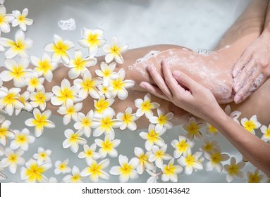 Woman legs in bath tube with flowers spa relaxation body care therapy concept