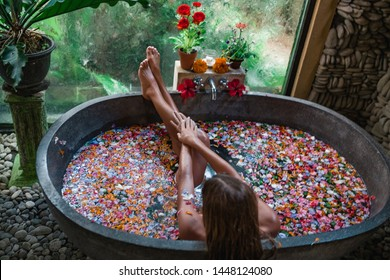Woman legs in bath tube with flowers spa relaxation body care therapy concept. Foot bath with flowersWoman relaxing in round outdoor bath with tropical flowers, organic skin care