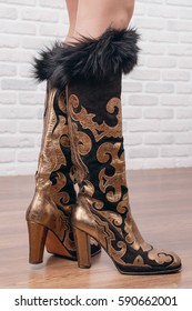 Woman legs in black gold high boots