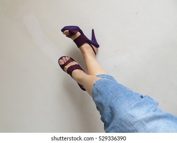 Woman legs in blue jeans pants and purple heels shoes.