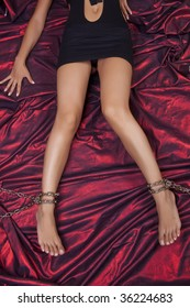 Woman Legs In Chains On Red Satin