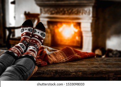 Woman legs with christmas sock on table and blurred home interior with fireplace. Free space for your decoration and dark mood photo style.